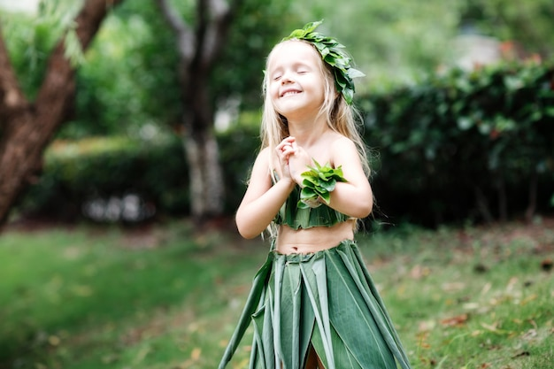 屋外の緑の草で作られたカーニバル衣装でかわいい金髪少女
