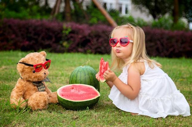 Маленькая девочка со светлыми волосами в солнечных очках ест арбуз в парке, рядом сидит плюшевый мишка