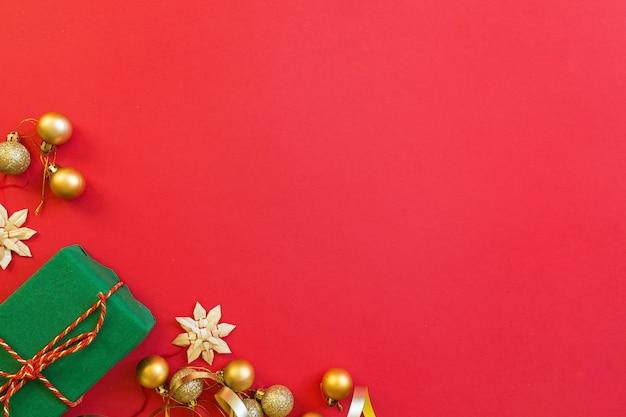Подарок, золотые игрушки лежат на красном фоне