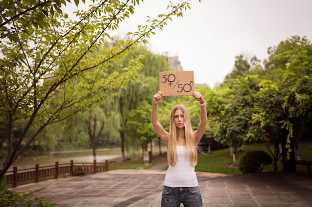 Женщина держит лист бумаги с символом мужского и женского пола