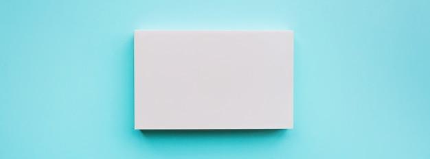 青い背景上に空白のピンクの紙