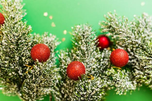 紙吹雪と緑の背景にクリスマスツリーの枝