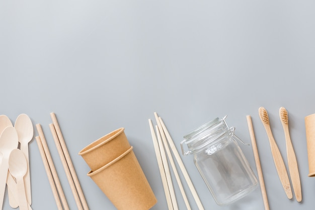 Эко натуральные бумажные стаканчики, соломка, деревянные столовые приборы плоские лежали на сером