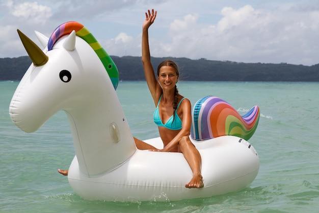Молодая красивая девушка с стройной фигурой в синем купальнике отдыхает и загорает на море