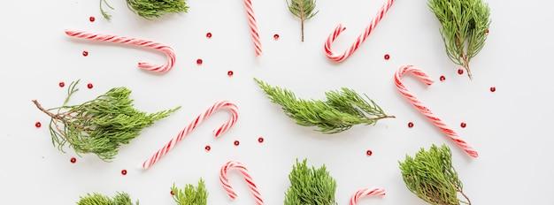 Рождественские еловые ветки и леденцы на белом