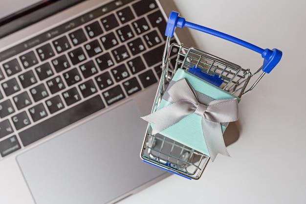 Плоская планировка с ноутбуком, продуктовой тележкой и подарочной коробкой