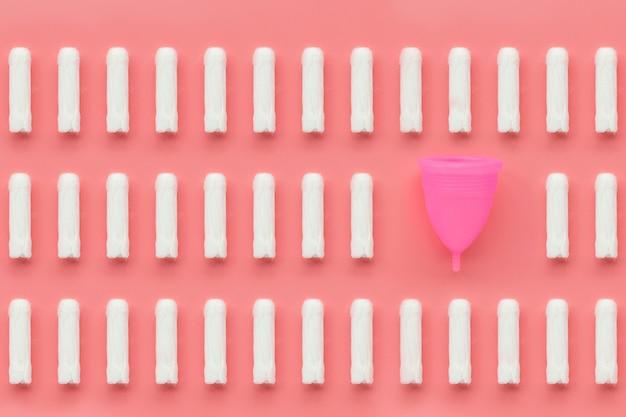 月経カップとピンクの背景のタンポン