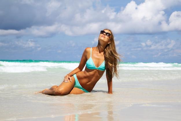 白い砂の上で日光浴青いビキニの若い女性の半ばセクション。熱帯のビーチで日焼けのファッションの女の子
