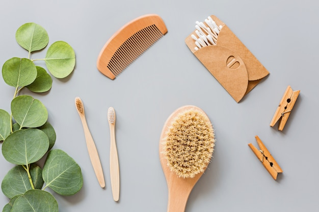 自然なバスルームアクセサリー:木製の櫛、竹歯ブラシ、マッサージブラシ、灰色の紙の背景に耳の棒。廃棄物ゼロ。