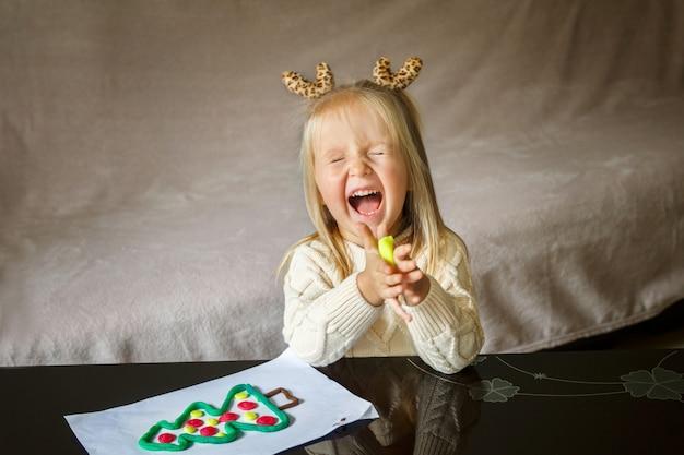 Маленькая девочка играет с глиной
