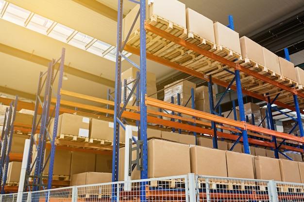 Большой ангарный склад промышленных и логистических компаний. длинные полки с разнообразными ящиками. промышленное пространство и аппаратная коробка для доставки, бизнес-логистики распределения хранения грузов концепции.