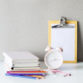 Снова в школу на белом столе. книги, карандаши, будильник на столе.
