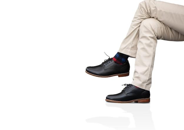 男性は男性のコレクションの服に長いズボンと黒い革の靴を着ています