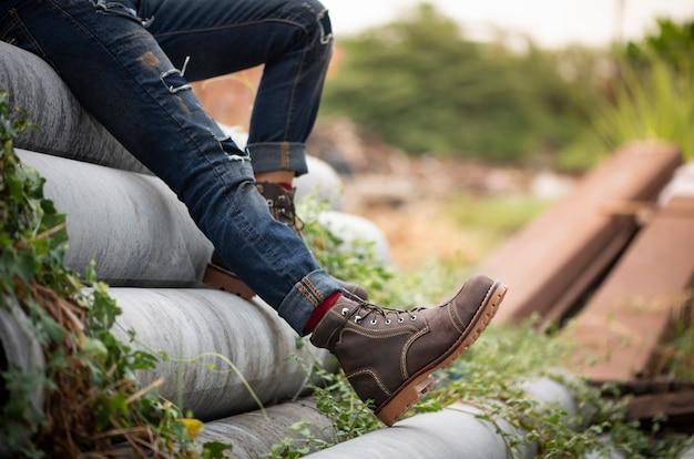 Модель одета в джинсы и коричневые сапоги из кожи для мужской коллекции.