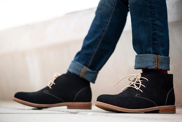 Модель одета в синие джинсы и черные ботильоны для мужской коллекции.