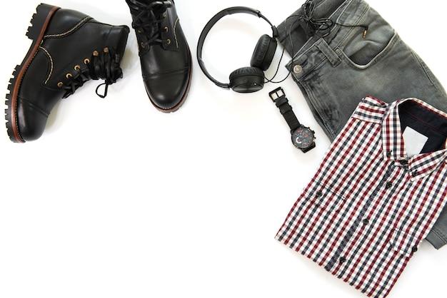 黒いアンクルブーツ、時計、イヤホン、灰色のジーンズ、白い背景、平面図、コピースペースで分離されたシャツと男性服の男性のカジュアルな服装