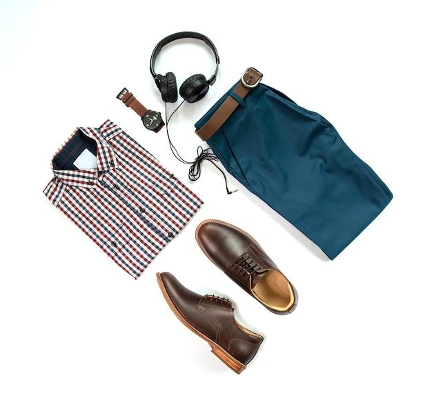 Мужские повседневные наряды для мужской одежды с коричневыми туфлями, часами, поясом, брюками, рубашкой и наушниками на белом фоне, вид сверху