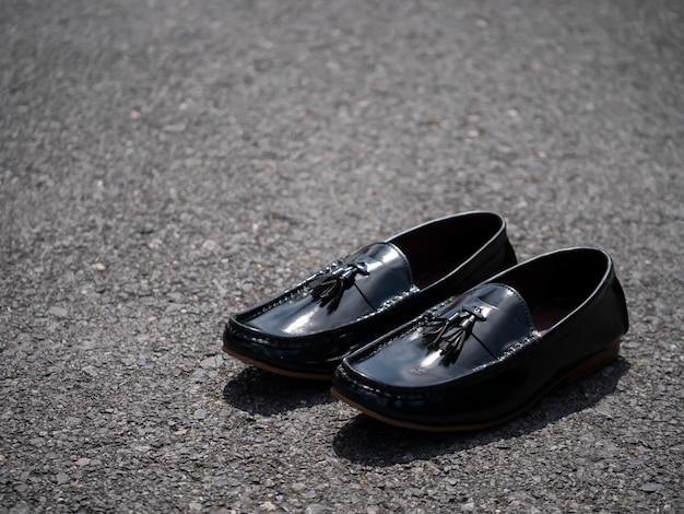 男性は床に黒い靴をファッションします。