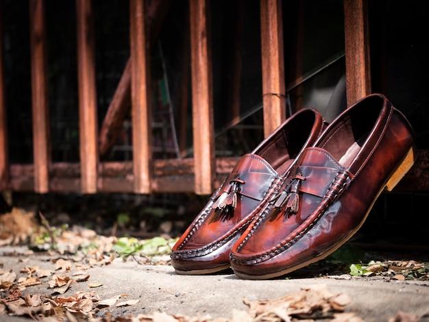 男性は床に茶色の靴をファッションします。