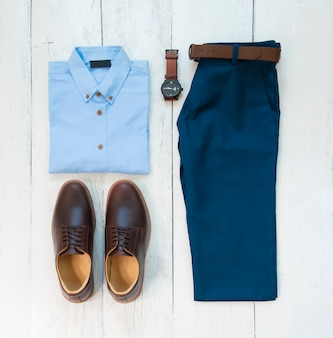 Комплект мужской одежды с коричневыми туфлями, брюками, поясом, часами и солнцезащитными очками, изолированными на белом деревянном фоне, вид сверху