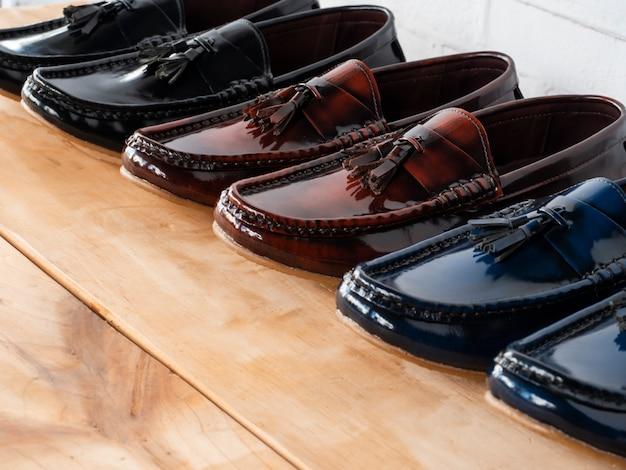男性は、販売のための靴屋で木の上のタッセルローファーの靴をファッション。