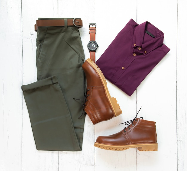 白い木製の背景、トップビューで分離された茶色のブーツ、時計、ズボン、ベルト、オフィスシャツと男性服の男性のカジュアルな服装