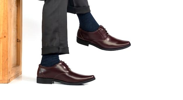 Элегантный мужчина в деловом платье в коричневых туфлях сидит на деревянной коробке и отдыхает на ноге