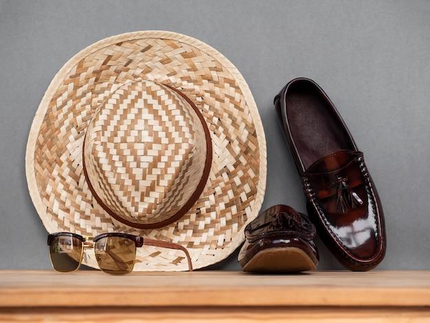 木製のテーブルに茶色の靴と男性ファッション夏服コンセプト