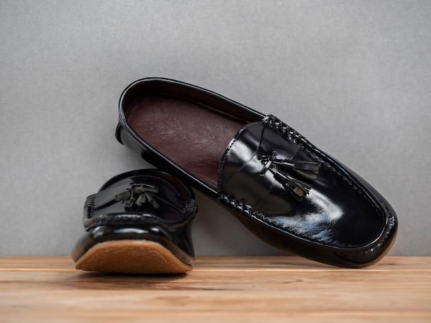 木製のテーブルに黒の男性ファッションタッセルローファー靴