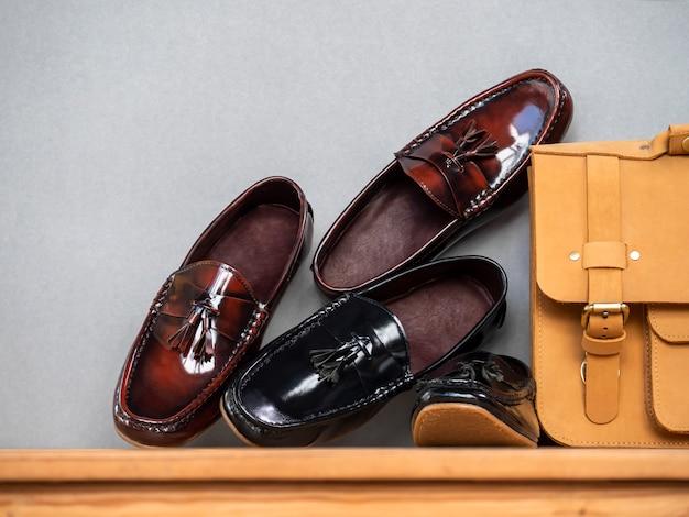 木製のテーブルに黒と茶色の男性ファッションタッセルローファー靴