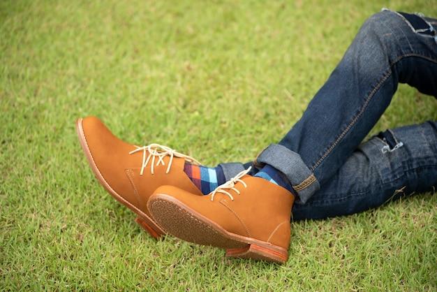 Укомплектуйте личным составом фотомодель нося коричневые кожаные ботинки и джинсы сидя на траве.