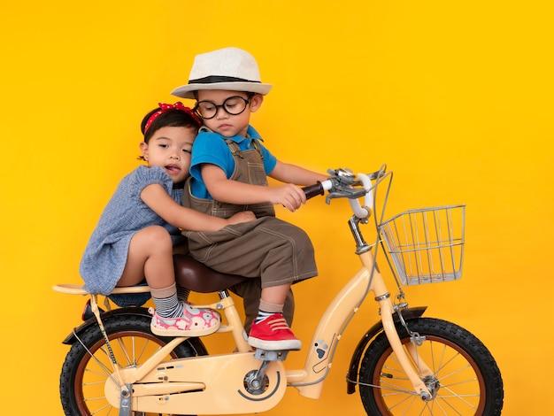 Дошкольный мальчик и девочка едут на велосипеде