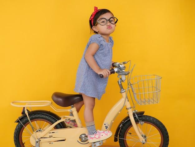 Азиатская девушка дошкольного возраста едет на велосипеде