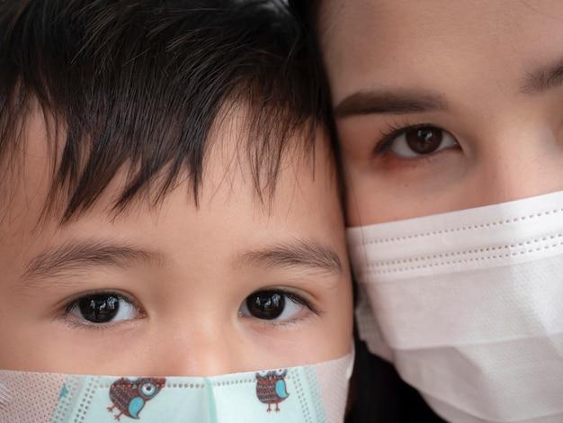 Крупный план азиатской семьи показывая влюбленность и нося защитную маску
