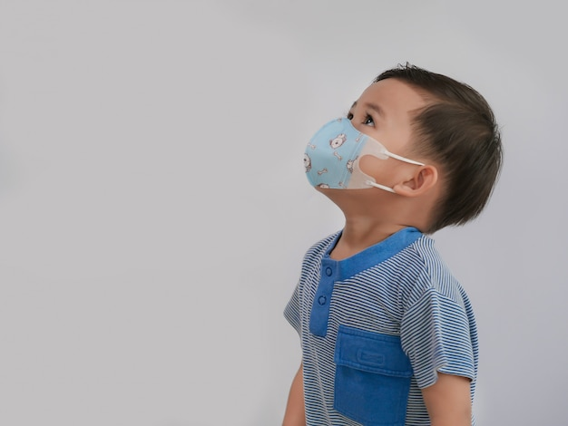Портрет азиатского мальчика смотря вверх и нося маску для того чтобы защитить от коронавируса.