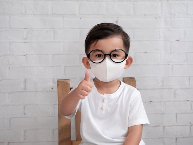 Портрет азиатского мальчика, показывая большой палец вверх и носить защитную маску, пытаясь защитить от коронавируса