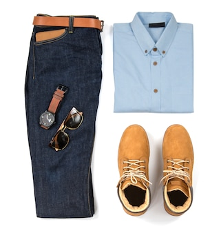 青いシャツ、ブルージーンズ、ベルト、時計、サングラス、白い背景、トップビューで分離された黄色のブーツと男性服の男性のカジュアルな服装
