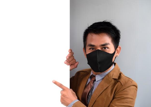 男性の手の人差し指がポインティングボードとマスクを着用し、コロナウイルスから保護しようとしている