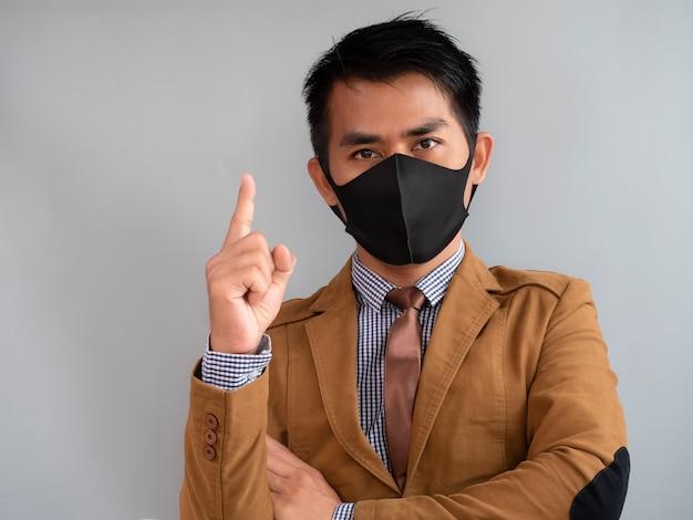 男性の手の人差し指が上向きで、コロナウイルスから保護しようとするマスクを着用