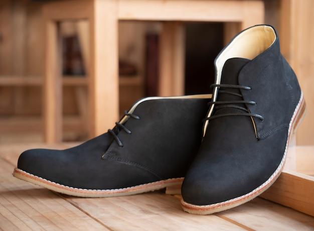 Мужские модные черные сапоги кожаные в магазине обуви.
