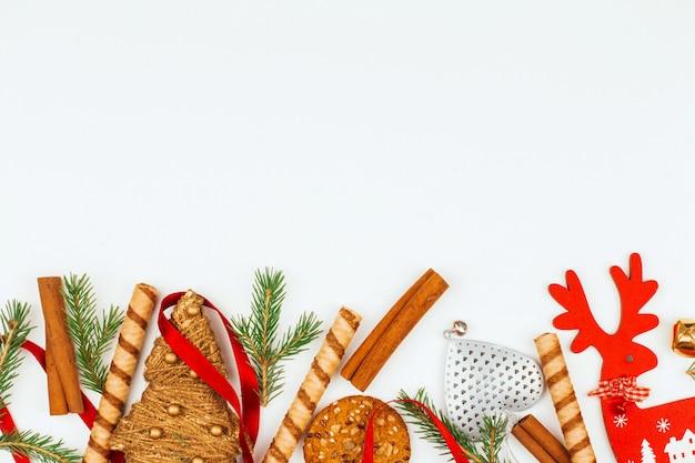 Елочные игрушки, сладости, еловые ветки и палочки корицы