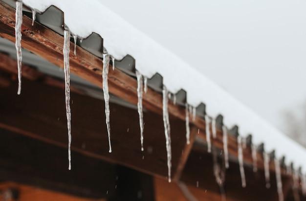 つららが木造住宅の屋根の軒先に掛かっている