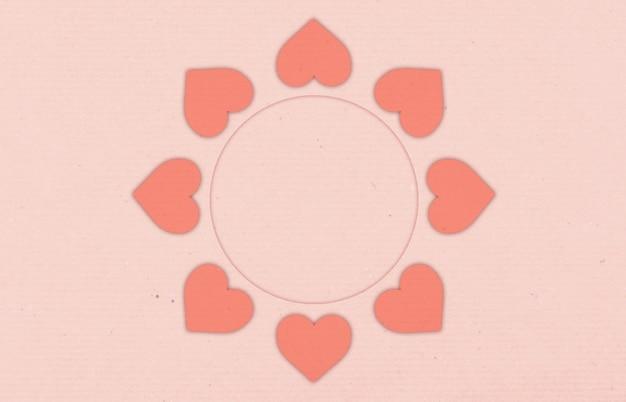 心とストライプの紙テクスチャコピースペースのラウンドフレームとピンクの背景。
