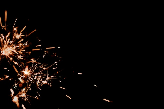 Бенгальские огни на черном фоне изолированных копией пространства.