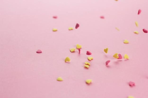 Падающие желтые и розовые кондитерские конфетти в форме сердца на розовом фоне копией пространства