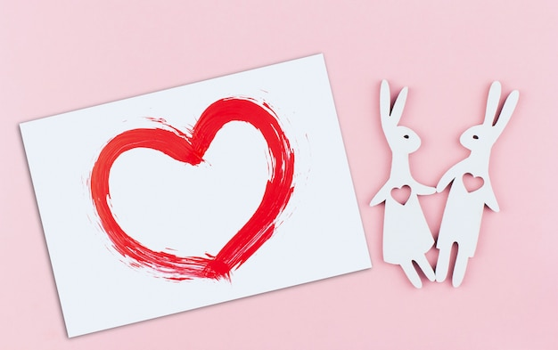 Белая карточка с нарисованным красным сердцем и пара кроликов с сердечками в груди на розовом фоне копией пространства