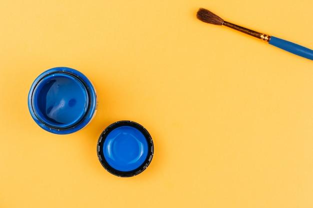 オレンジ色の背景に青いアクリル絵の具とブラシの瓶。アートペイント。