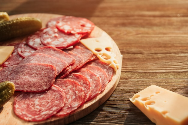 Тонкие ломтики колбасы, сыра и маринованных огурцов на круглой разделочной доске на деревянном столе. русская закуска.