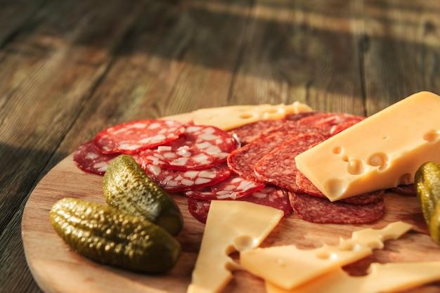 Ломтики сыра с большими отверстиями, нарезанная колбаса и маринованные огурцы на деревянной доске.