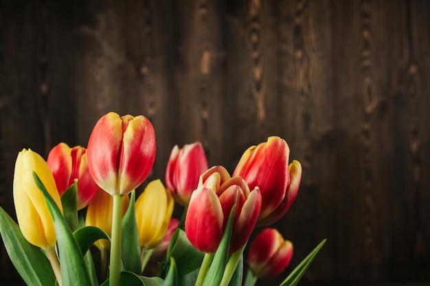 茶色の木製の背景コピースペースに赤、黄色、ピンクのチューリップの花束。古い木製のテーブルフラットにチューリップを置きます。